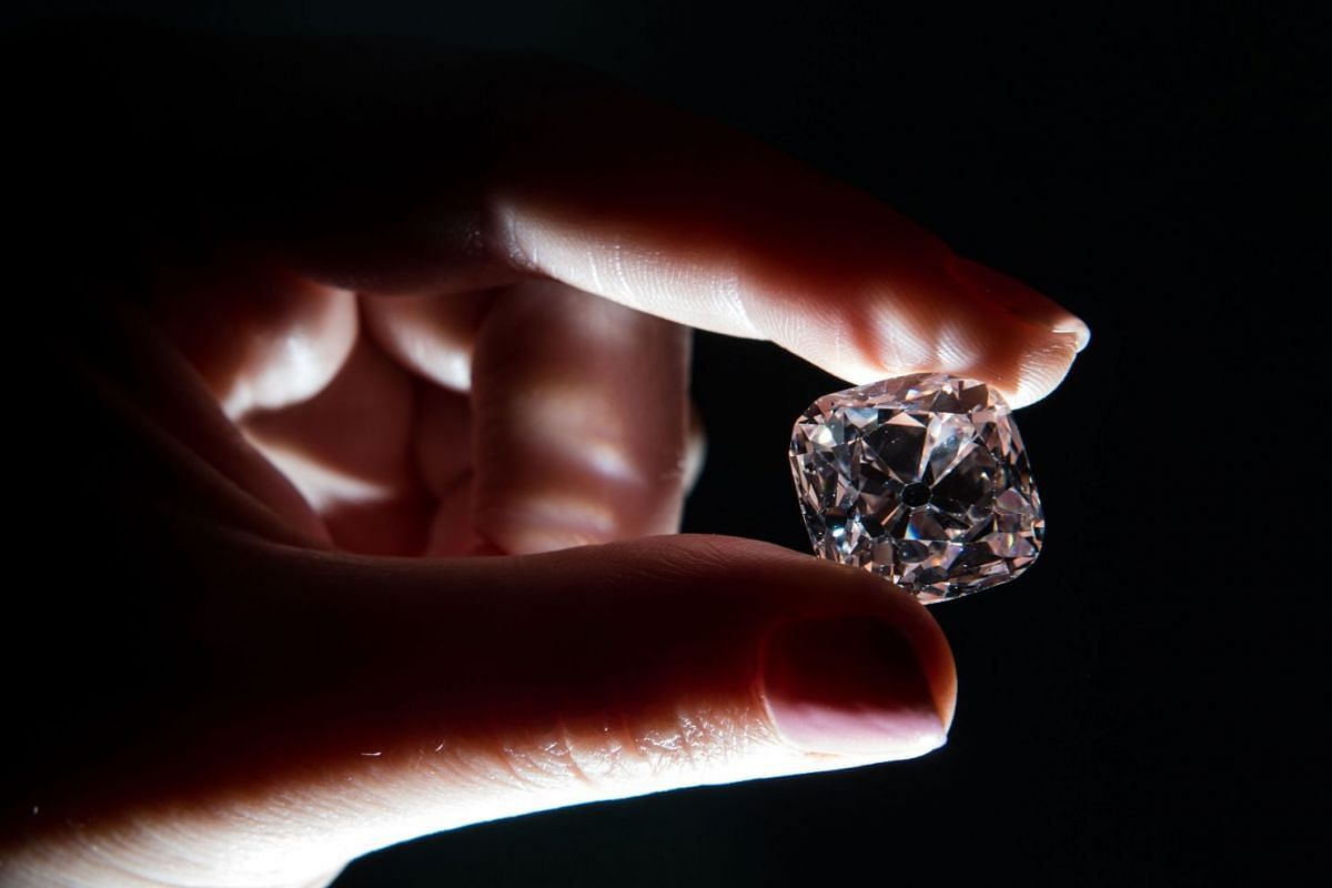 A woming holds the 'Le Grand Mazarin', a 19,07 carat pink diamond, at Christie's auction house in London.