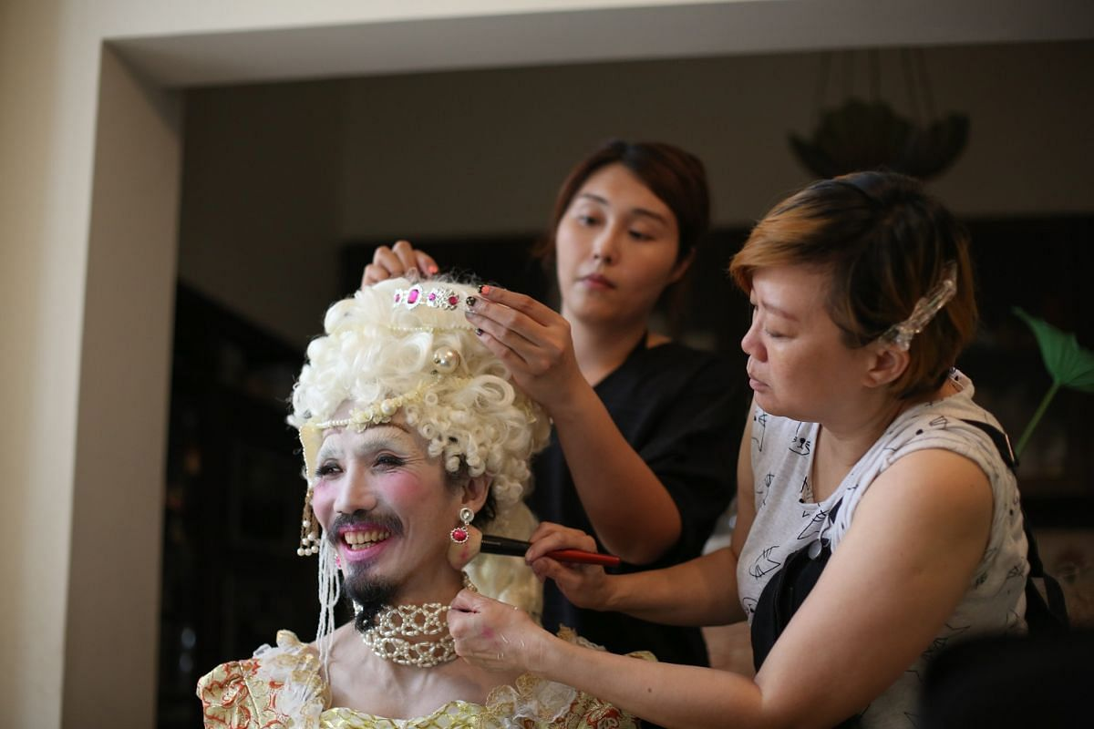 A team of about 20 friends and collaborators work with Yang Derong on the Face Of The Day project. Ms Zennie Casann (far left) and Ms Carol Yoong of Zenmakeup are dressing him up as Queen of France Marie Antoinette.