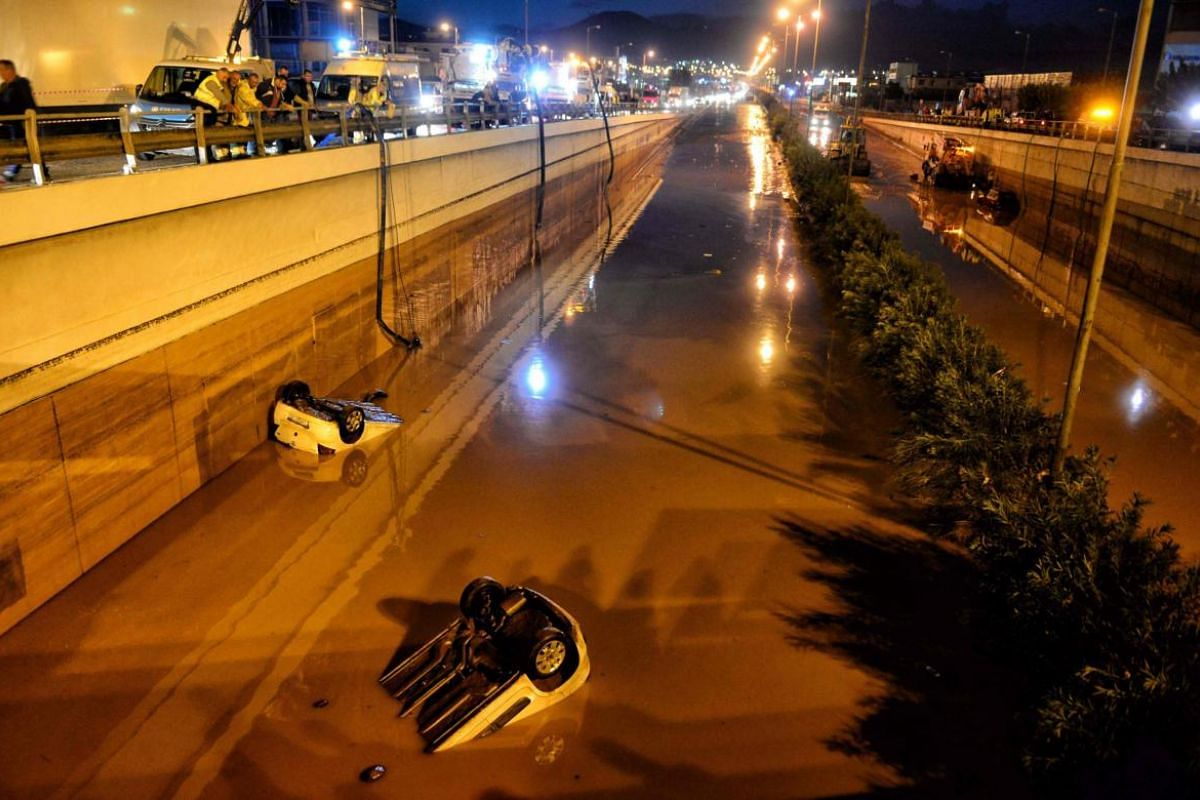 Bystanders and rescue personnel look at vehicles submerged in floodwaters on a highway near Eleusina, south-west of Athens.