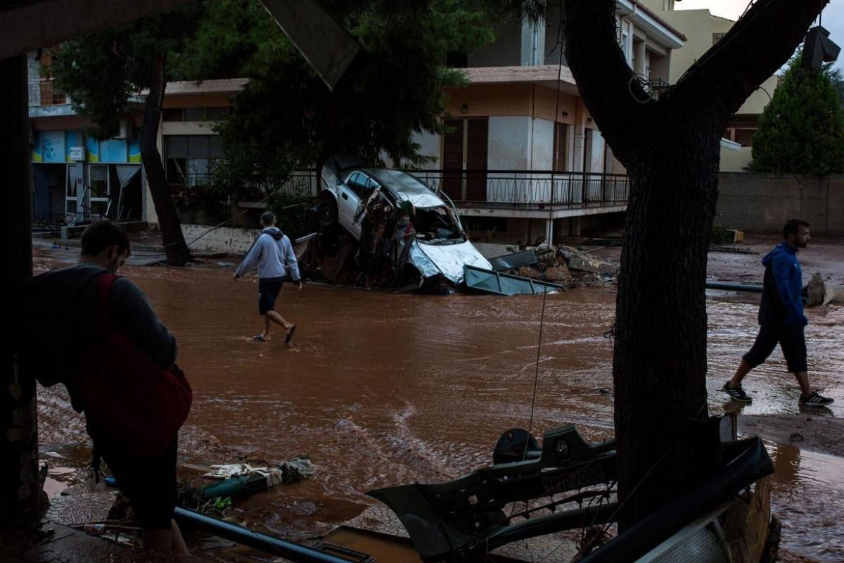 People walk past a wrecked car in a flooded street in the town of Mandra, northwest of Athens.