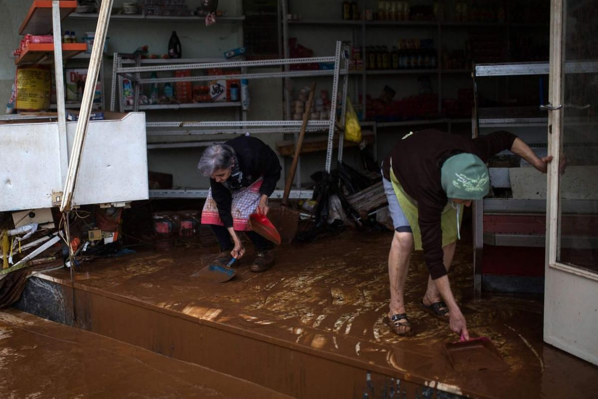 Women clean mud from the floor of a shop in the town of Mandra, northwest of Athens.