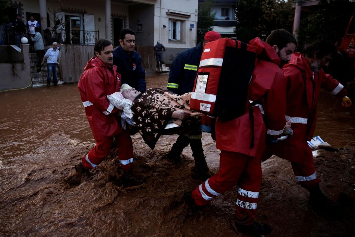 Hellenic Red Cross volunteers and firemen evacuate an elderly man following heavy rainfall in the town of Mandra.