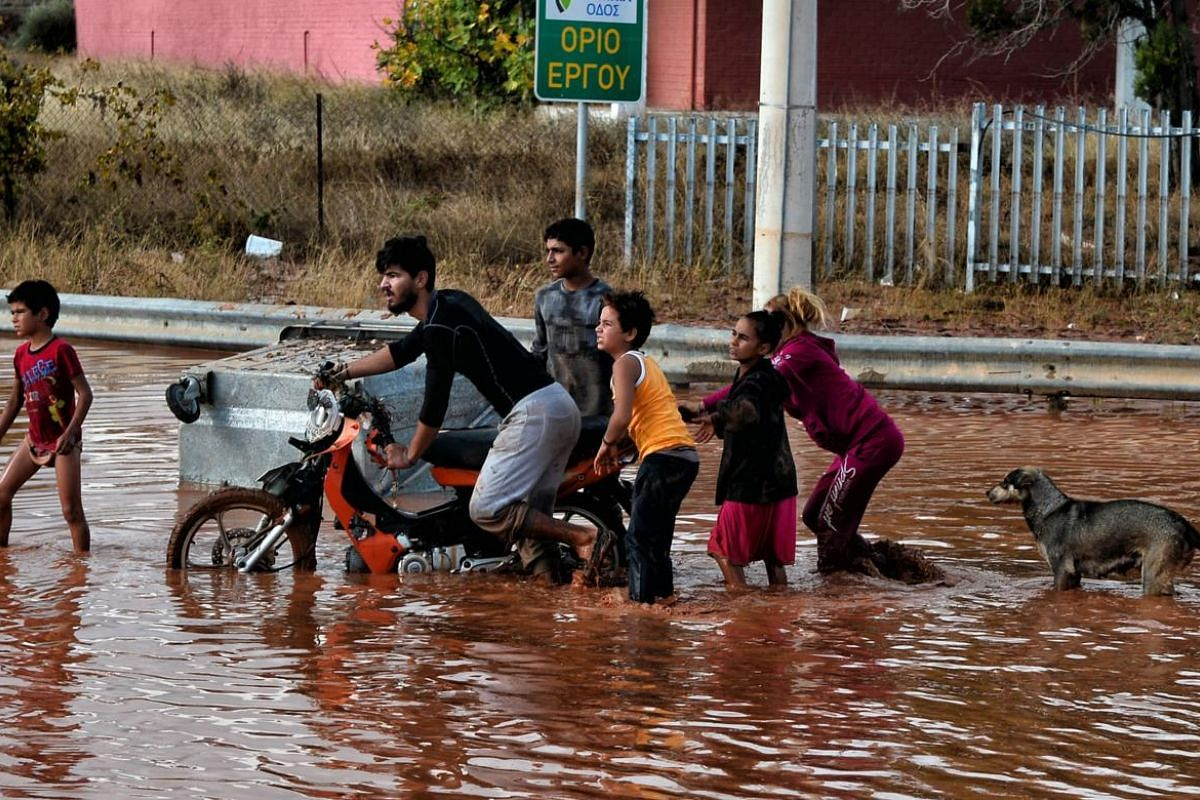 People make their way on a flood street in Mandra.