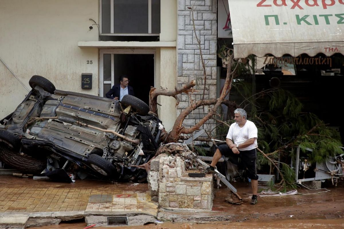 Locals stand next to destroyed car following a heavy rainfall in the town of Mandra, Greece.