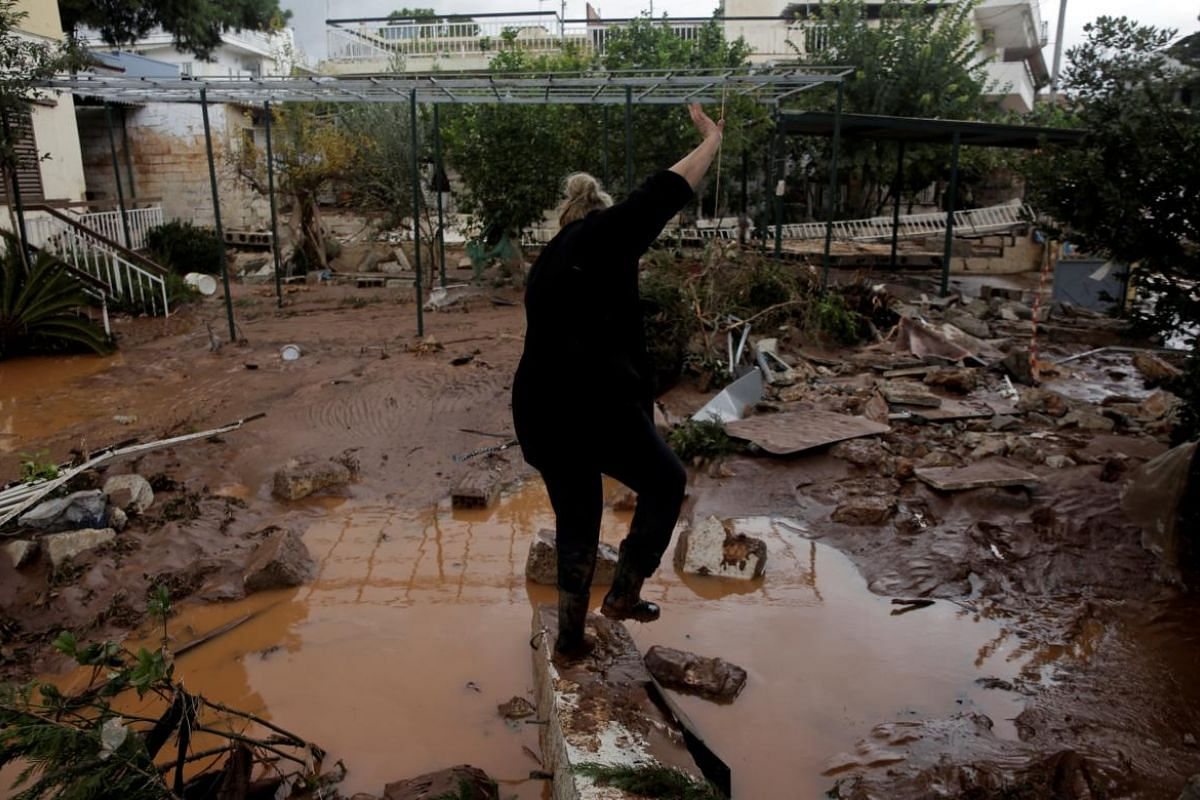 A local stumbles as she walks on debris in a yard, following a heavy rainfall in the town of Mandra.