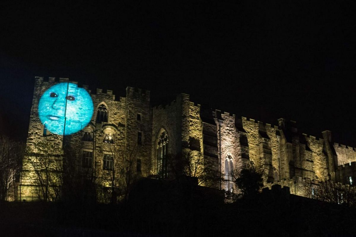 A light art installation entitled 'Our Moon' by artist Hannah Fox is projected onto the walls of Durham Castle.