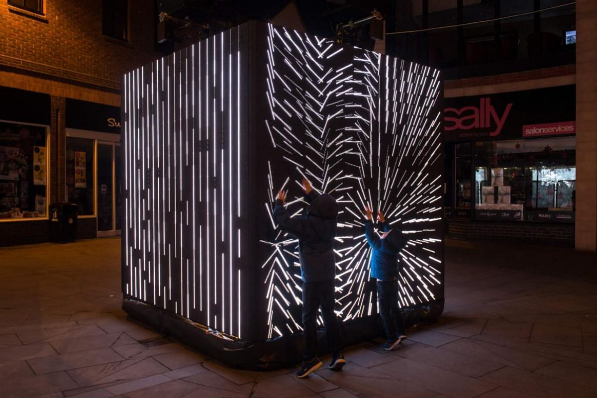 Members of the public interact with a light art installation entitled 'Control No Control' by artist Daniel Iregui.