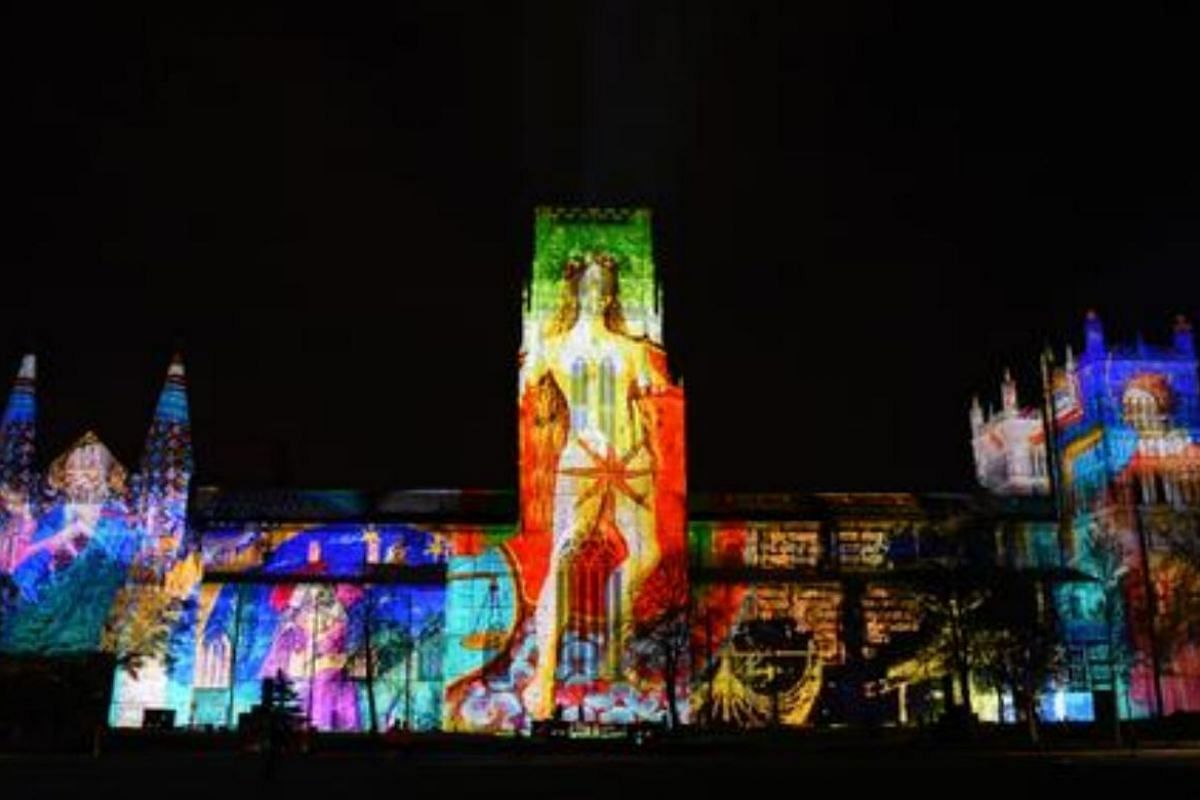 A light art installation entitled 'The World Machine' is projected onto the facade of Durham Cathedral.