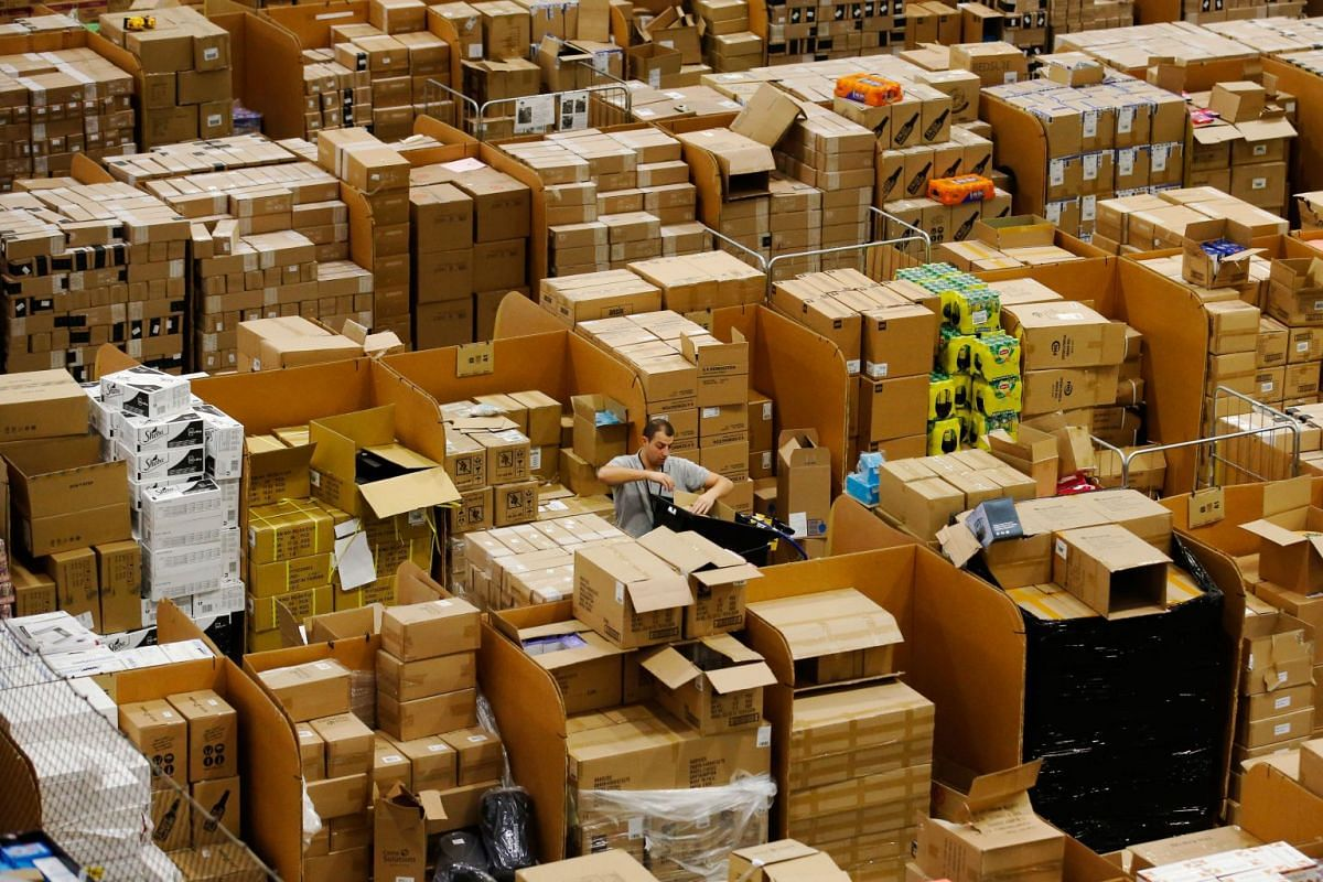 A worker picks an item for a customer's order at an Amazon.com Inc. fulfillment center in Peterborough, U.K., on November15, 2017. As Amazon's share of retail sales grows, its corporate stewardship is coming under greater scrutiny.