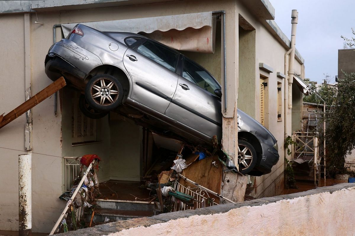 A cars is stuck on the entrance of a house in Mandra, Western Attica, Greece November 16, 2017. Civil Protection said that six people are still missing in Western Attica, following the flash floods that hit the region the previous day. According to r
