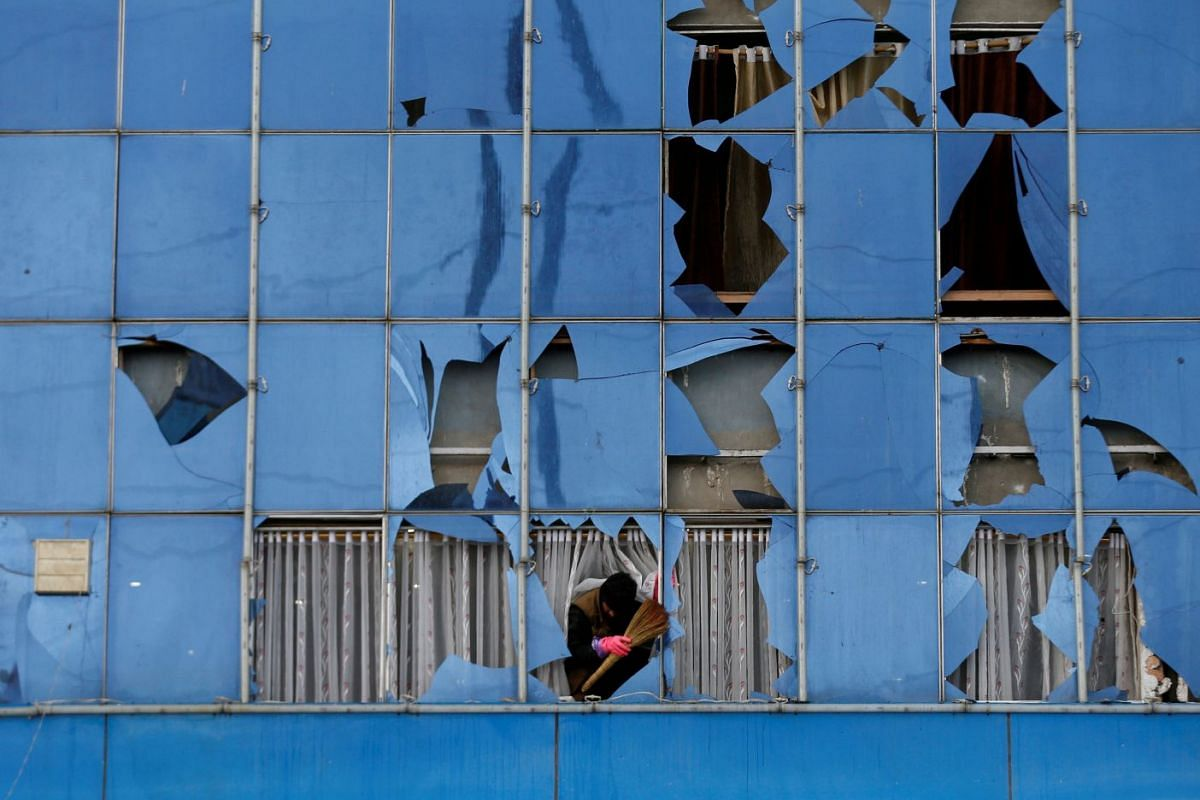 A man removes broken glass from a building after a suicide bomb attack in Kabul, Afghanistan November 16, 2017.