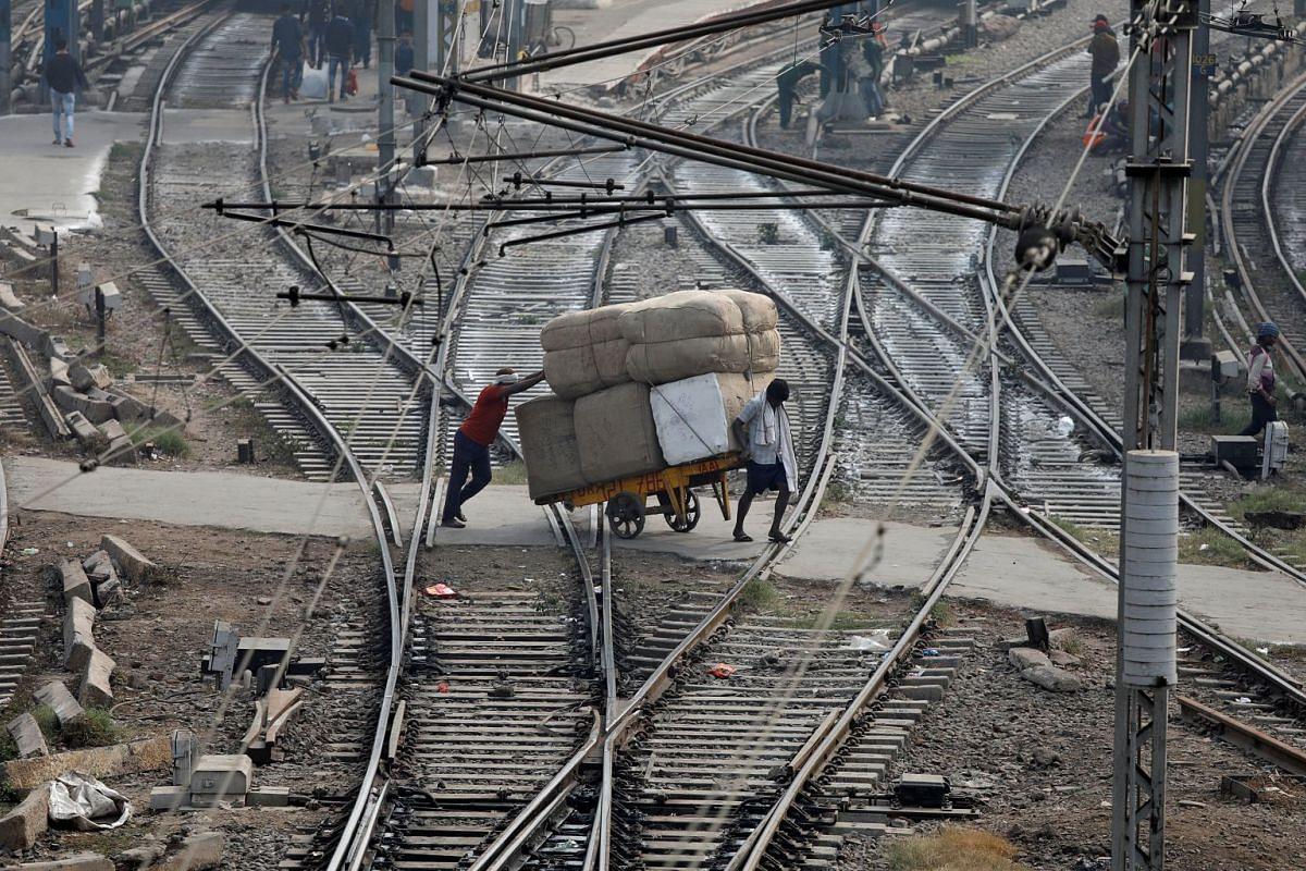 Men transport goods across railway tracks in New Delhi, India, November 16, 2017.