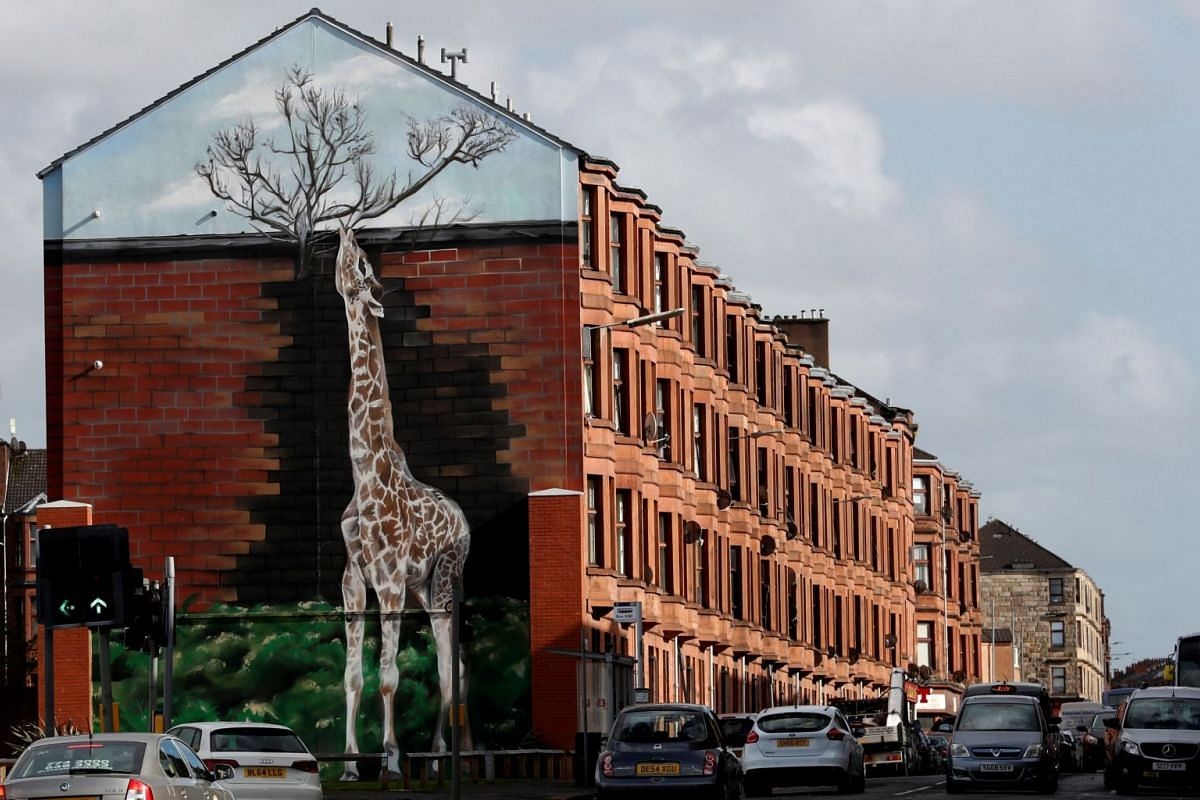 A giraffe mural is seen on the gable end of a building in Shettleston Road in Glasgow East, in Glasgow, Scotland, September 29, 2017.