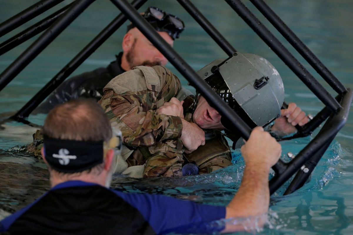 Soldiers from the 1st Armored Division, Combat Aviation Brigade, train on how to react if a helicopter crashes into the water before heading to Puerto Rico in order to aid in recovery efforts following Hurricane Maria at Fort Bliss in El Paso, Texas,