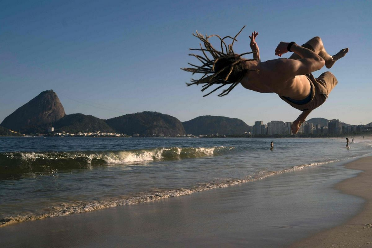 German national Alex Leist, jumps backdropped by the Sugar Loaf mount during his mixed training of Brazilian capoeira fight and acrobatics at Flamengo beach in Rio de Janeiro, Brazil, on November 16, 2017.
