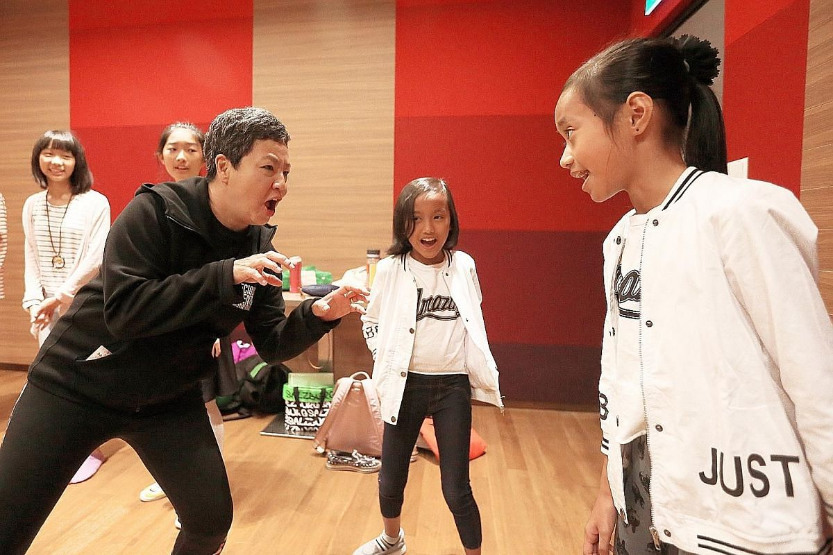 From far left: Mikey Robinson, 12, and Bastien Buwalda, 12, clown around as Verlene Chew, 12, adjusts 12-year-old Natanya Tan's hat, and Laura Maurer-Stroh, 10, waits in a room with other performers for a full-dress rehearsal to begin last Saturday.