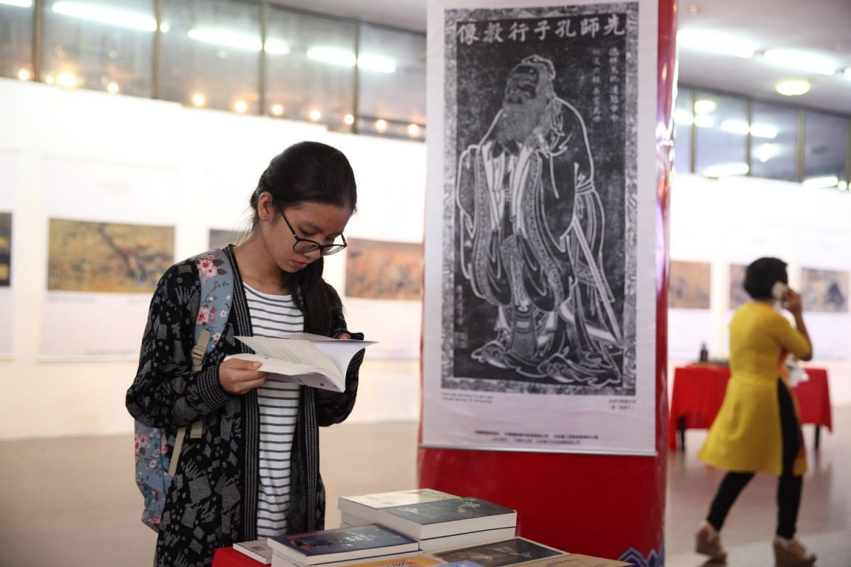 A woman browsing the books on display during a cultural exhibition on famed Chinese sage Confucius in Hanoi earlier this month. Beijing's stepped-up efforts to promote itself and get its message across have been felt in all corners of the world.