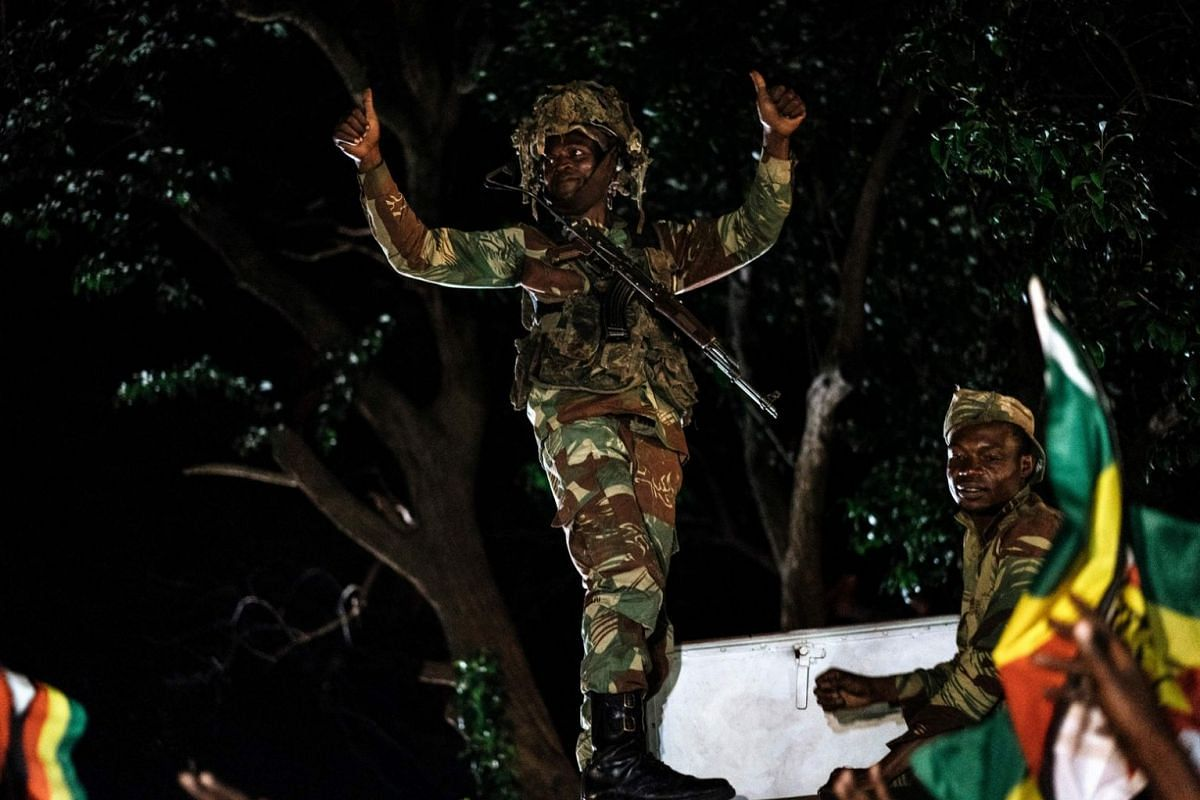 A Zimbabwean soldier gestures as people celebrate after the resignation of President Mugabe, on Nov 21, 2017.