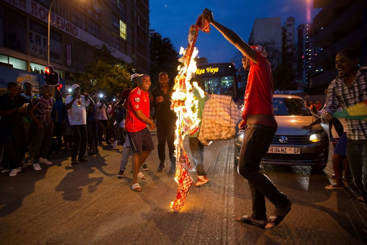 Zimbabweans living in South Africa celebrate by burning a banner with Robert Mugabe's image after President Robert Mugabe resigned, in South Africa on Nov 21, 2017.
