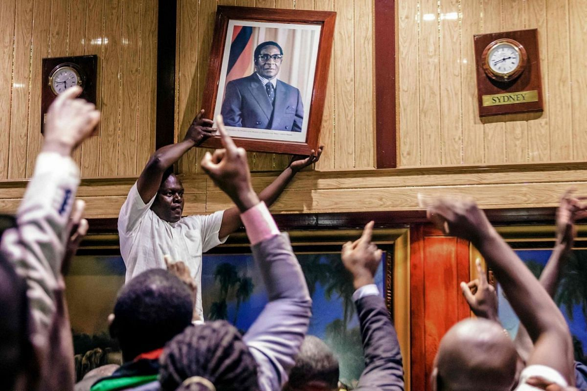 People remove the portrait of former Zimbabwean President Robert Mugabe from the wall at the International Conference centre, where parliament had their sitting, after his resignation on Nov 21, 2017.