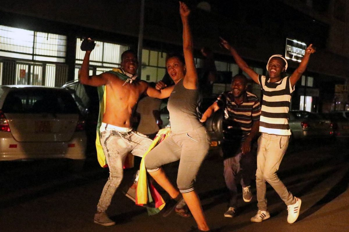Zimbabweans celebrate on the streets of Harare after President Robert Mugabe resigned on Nov 21, 2017.