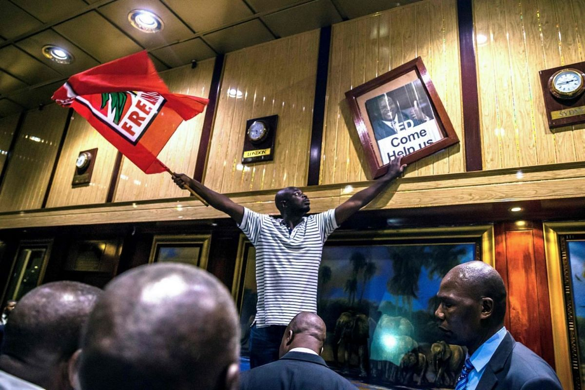 A man holds a Mozambican Liberation Movement flag and a poster with the portrait of former Zimbabwean deputy President Emmerson Mnangagwa after removing the portrait of former Zimbabwean President Robert Mugabe at the International Conference centre