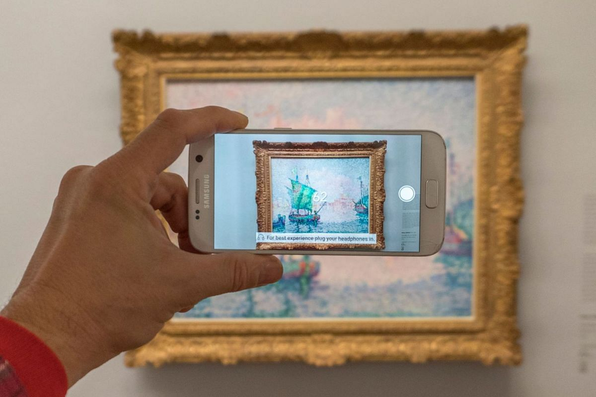 A visitor is looking at an animation as he points his smartphone at French painter Paul Signac's painting Venice, The Pink Cloud using the Artvive app at Albertina Gallery in Vienna, Austria on Nov 21, 2017. Albertina gallery unveiled 'an augmented r