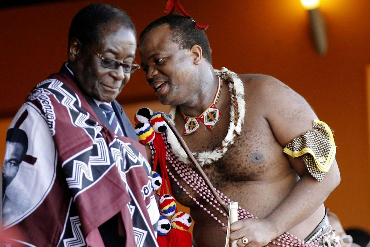 Former Zimbabwe President Robert Mugabe (left) chats with Swaziland's King Mswati III during the annual Reed Dance at Ludzidzini in Swaziland, on Aug 30, 2010.