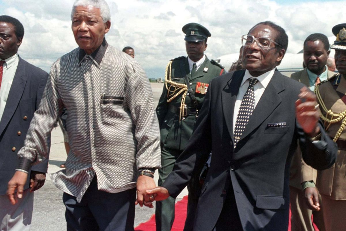 Former Zimbabwe President Robert Mugabe (right) holds hands with his South African counterpart Nelson Mandela, greeting him on his arrival in Harare, on Dec 13, 1998.