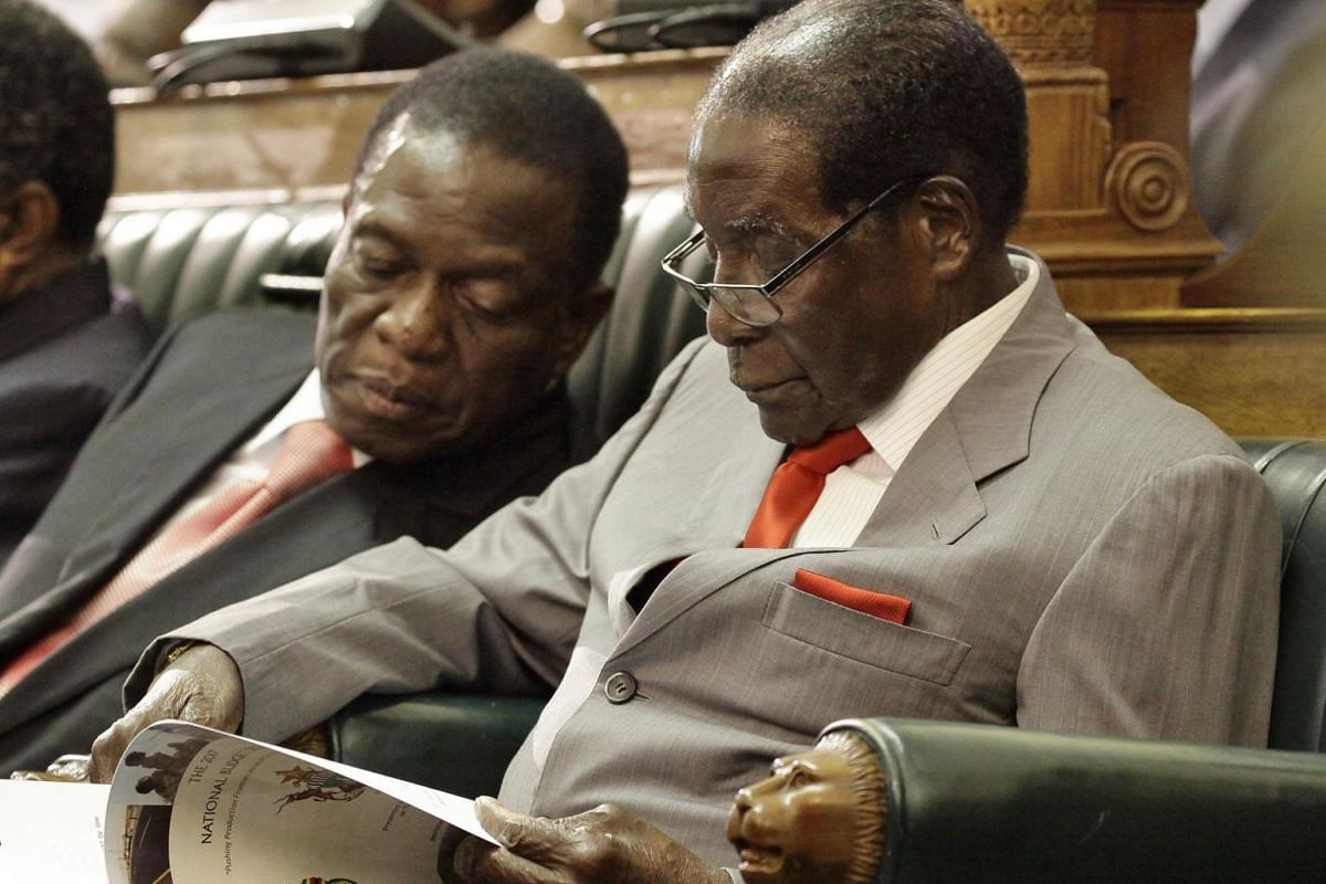 Former Zimbabwe President Robert Mugabe (right) is flanked by his then deputy Emmerson Mnangagwa (left) as he reads a copy of the country's 2017 National Budget in the house of parliament, in Harare, Zimbabwe, on Dec 8, 2016.