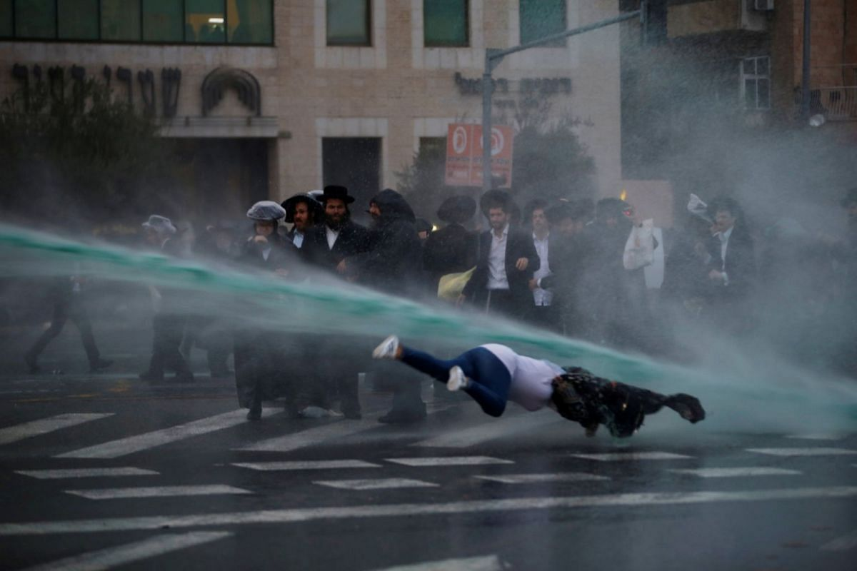 A bystander falls as Israeli police spray water during a demonstration by ultra-Orthodox Jews against the detention of members of their community who failed to report to a military recruiting office, in Jerusalem November 26, 2017. PHOTO: REUTERS