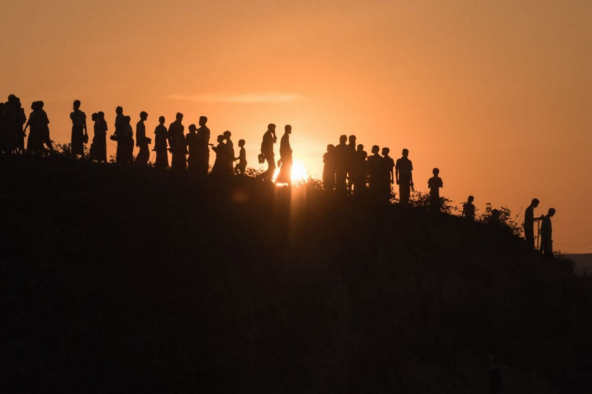 Rohingya Muslim refugees walk down a hillside in the Kutupalong refugee camp in Cox's Bazar on November 26, 2017. PHOTO: AFP