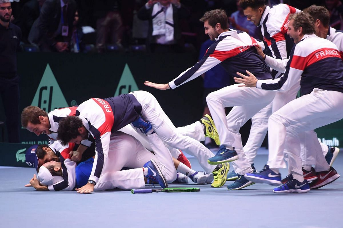 France's Lucas Pouille (bottom) celebrates with his teammates after winning his singles rubber 5 match against Belgium's Steve Darcis at the Davis Cup World Group final tennis match between France and Belgium at The Pierre Mauroy Stadium in Villeneuv