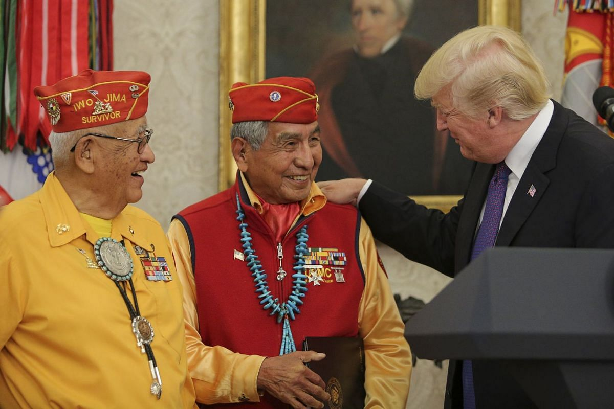 """U.S. President Donald Trump, right, speaks with World War II veterans during an event honoring Native American """"Code Talkers"""" inside the Oval Officer of the White House in Washington, D.C., U.S., on Monday, Nov. 27, 2017. PHOTO: POOL VIA BLOOMBERG"""