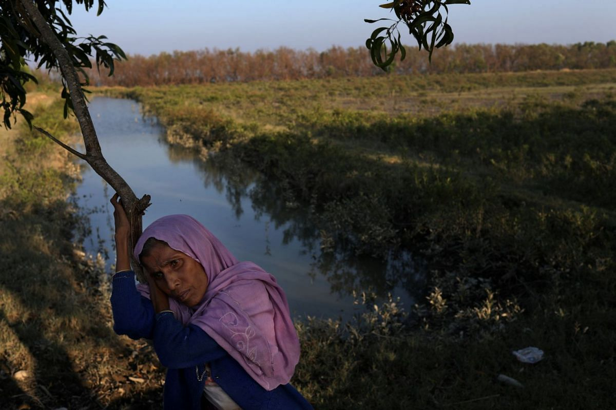 Rohingya refugee Amina Khatun, 55, rests at the bank of the Naf river after crossing it on an improvised raft to reach Bangladesh, in Teknaf, Bangladesh, November 27, 2017. Two of her sons were killed by gun fire when her village was attacked by Myan