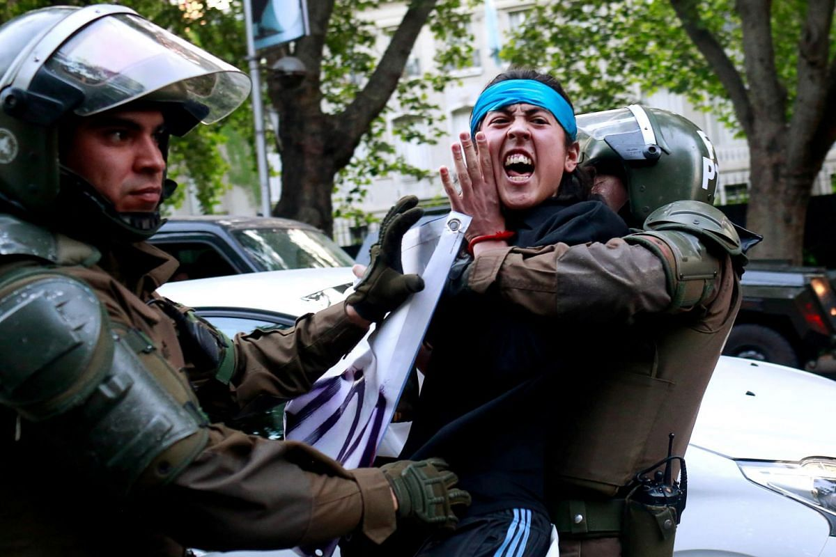 A Mapuche Indian activist is detained during a protest in support of Rafael Nahuel, a Mapuche Indian activist and Argentinian who was shot dead during clashes near Bariloche, southern Argentina according to local media, in Santiago, Chile, November 2