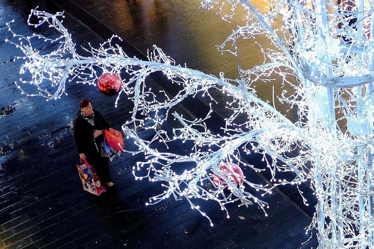 A woman holds shopping bags as she stands beneath Christmas decorations in Liverpool, Britain, on Nov 27, 2017.