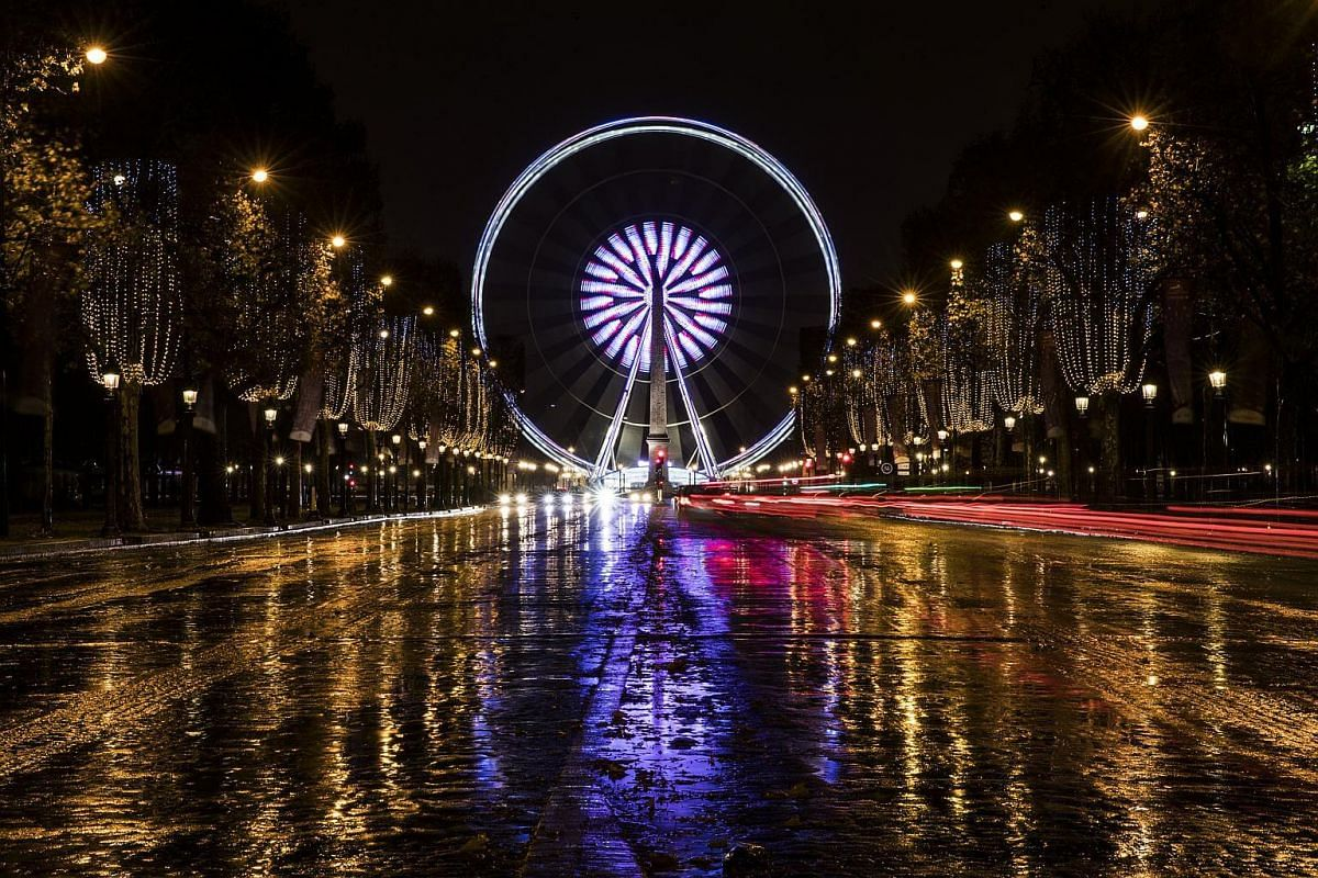 Christmas lights hang from the trees on a rainy night in the Champs Elysees avenue in Paris, on Nov 27, 2017.