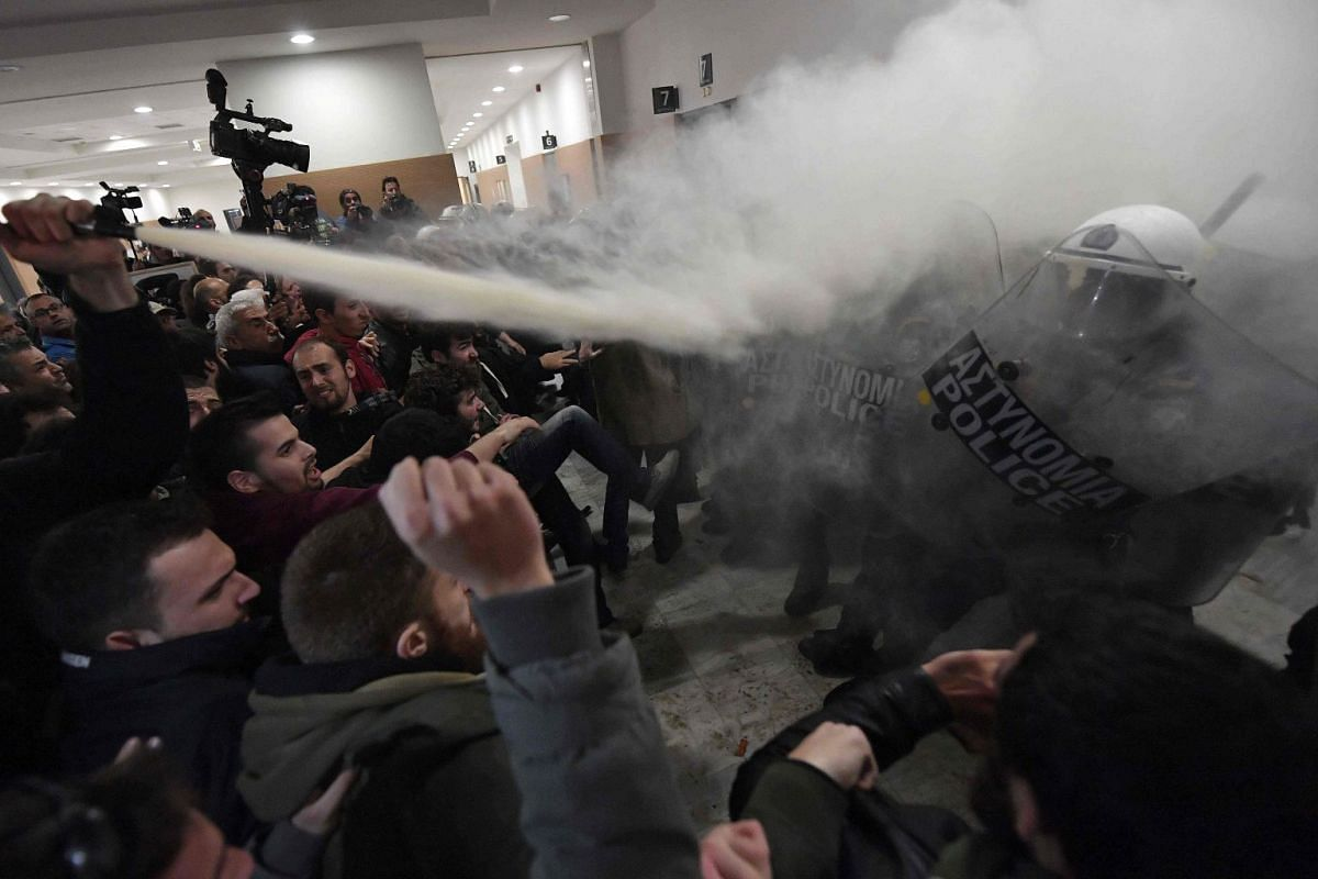 Protesters clash with riot police in the lobby of a courtroom in Athens on November 29, 2017. People protesting homes' auctions clashed with police at Athens court of appeals as foreclosures begin anew as part of reforms under Greece's bailout plans.