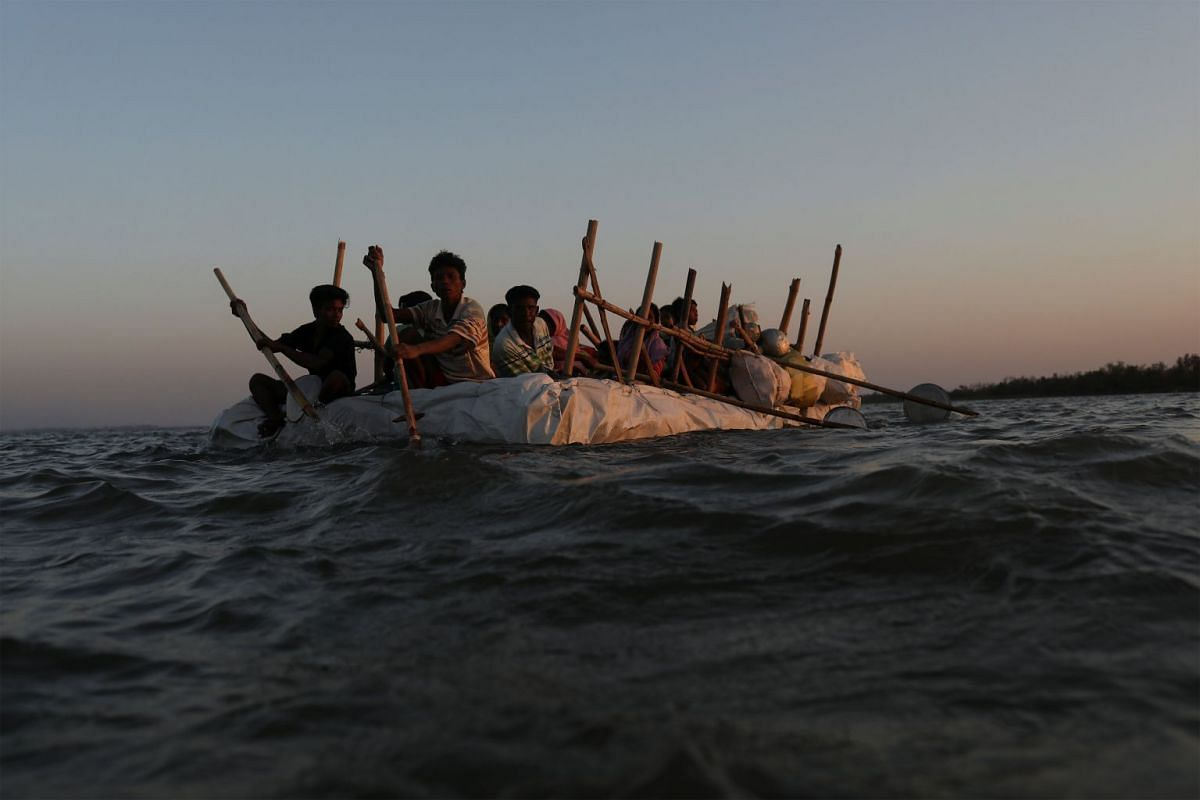 Rohingya refugees sail on an improvised raft across the Naf River to reach Bangladesh, in Teknaf, Bangladesh, November 29, 2017. PHOTO: REUTERS