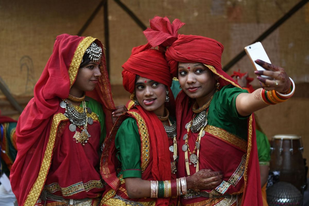 Indian artists from central India of Madhya Pradesh take selfie before performing in a cultural event organised by Indira Gandhi National Centre for Arts in New Delhi on November 29, 2017. PHOTO: AFP