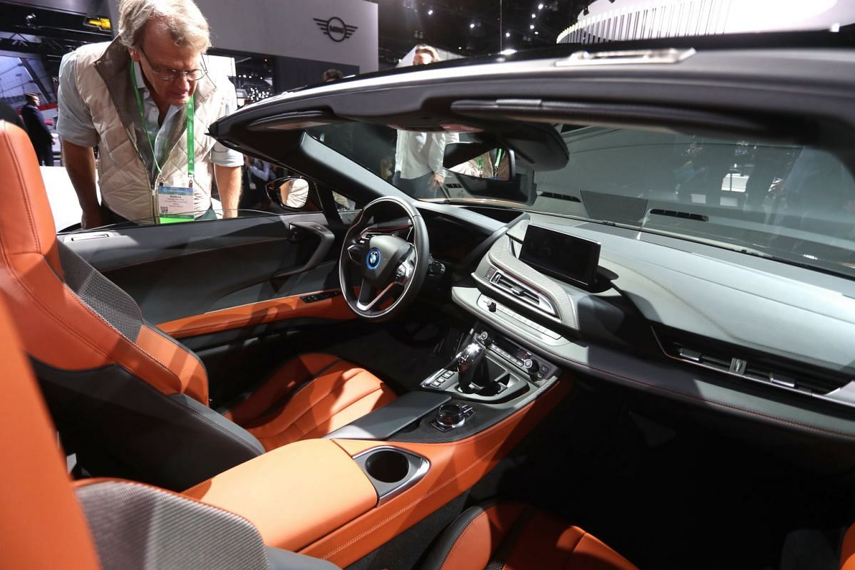 A visitor taking a look at the interior of the BMW i8 Roadster at the LA Auto Show on Nov 29, 2017.