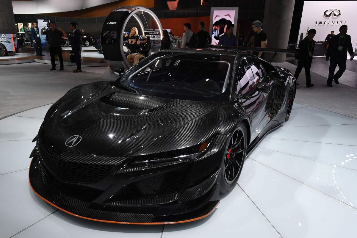 Visitors walking past the new Acura NSX-GT3 race car at the LA Auto Show in Los Angeles.