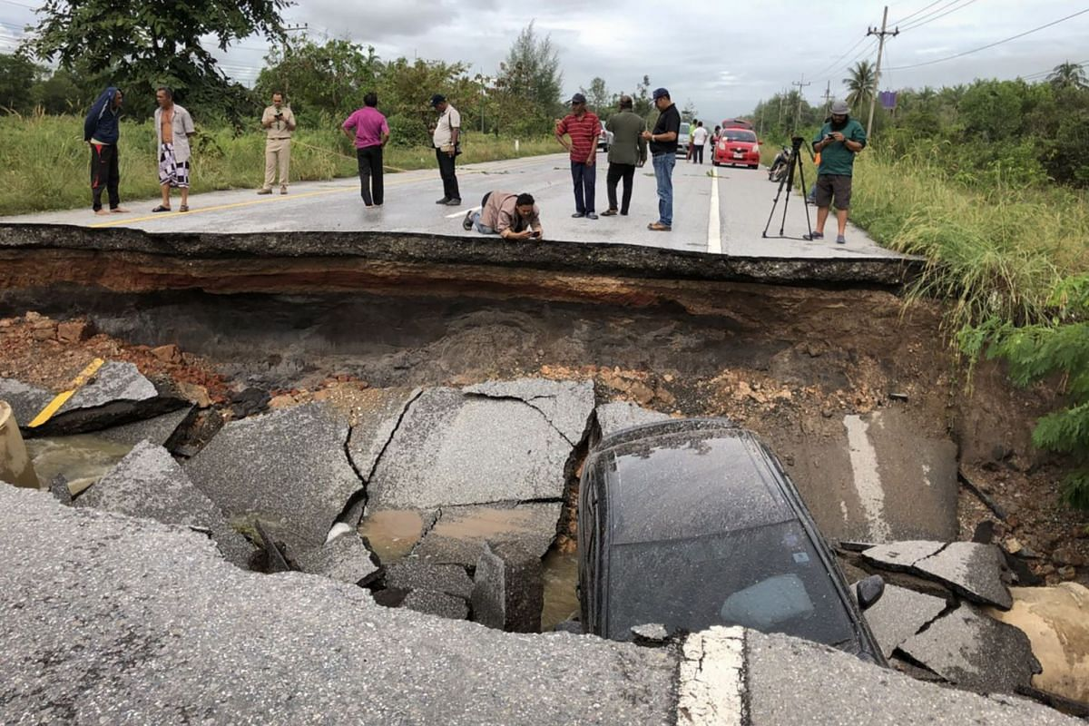 People take photos of a road that collapsed due to heavy flooding in the southern Thai district of Songkhla on Nov 30, 2017. PHOTO: AFP
