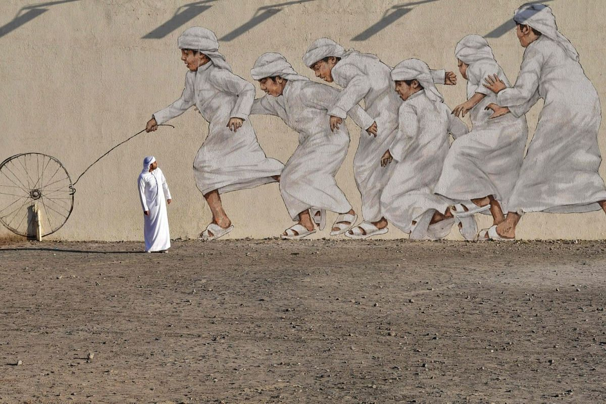 A man walks past a giant mural depicting boys running after a wheel, in Dubai on Nov 30, 2017. PHOTO: AFP