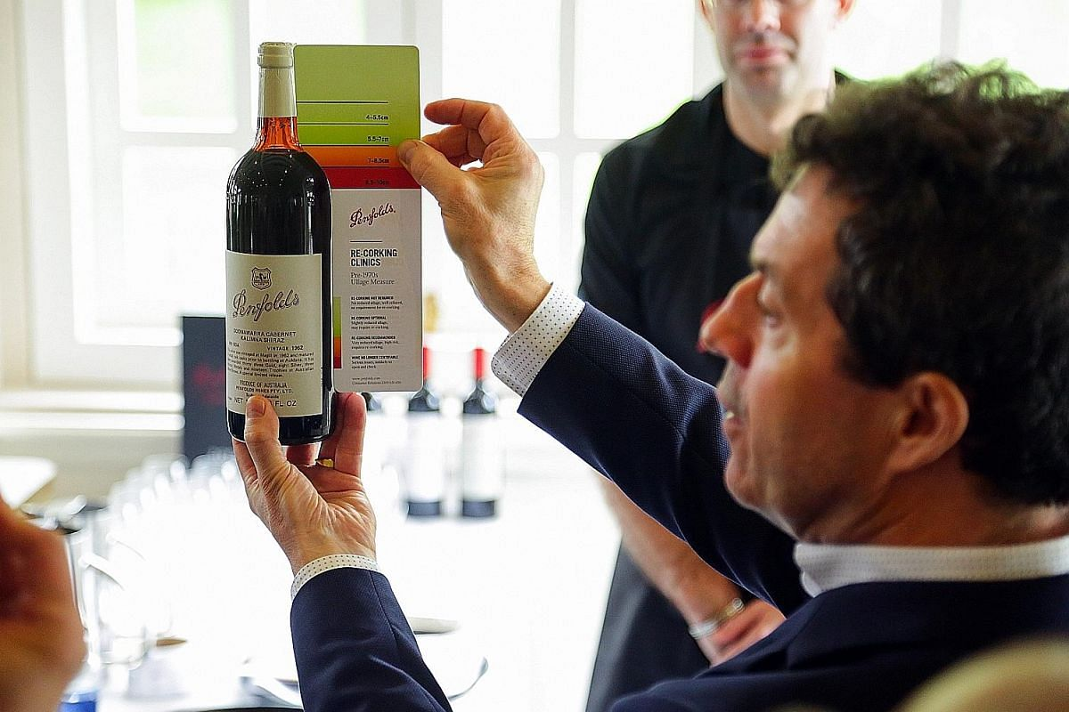 Mr Peter Gago holds up a card that helps determine the acceptable liquid level of a Penfolds bottle that is being assessed.