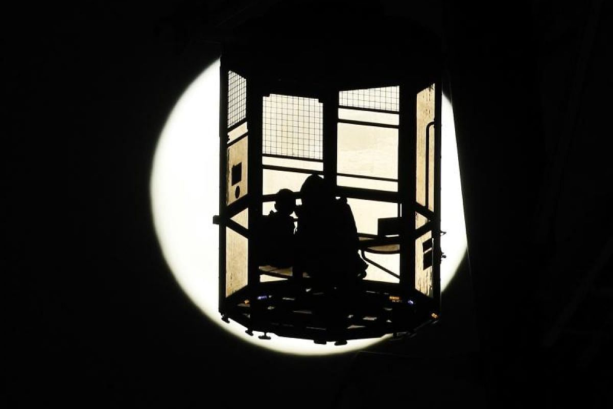 Visitors enjoy viewing the supermoon from a gondola of a ferris wheel at an amusement park in Tokyo.