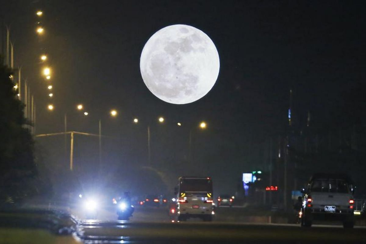 A supermoon dominates the sky while traffic rolls in the streets in Naypyitaw, Myanmar.