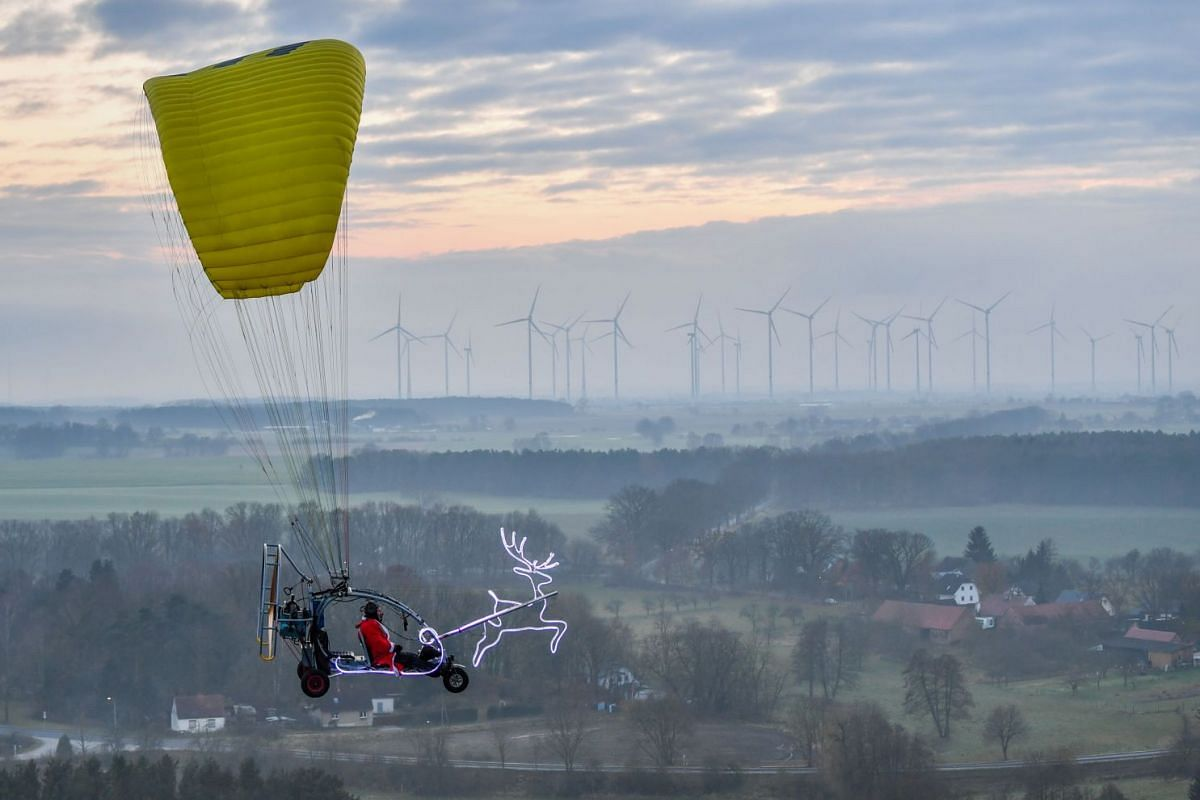 A man, disguised as Santa Claus, flies in a microlight on December 2, 2017 near Sieversdorf, eastern Germany. PHOTO: DPA VIA AFP