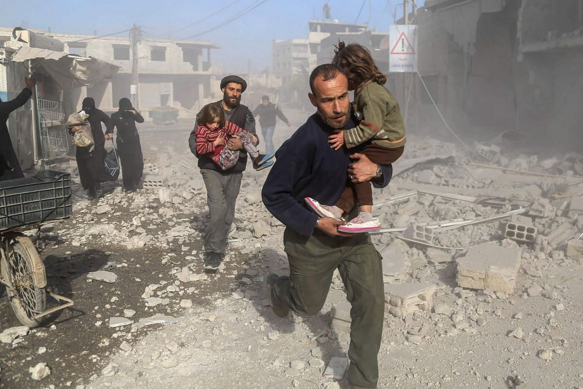 Syrians make their way through debris following a reported air strike in the rebel-held town of Beit Sawa, in the eastern Ghouta region on the outskirts of the capital Damascus, on December 3, 2017. PHOTO: AFP